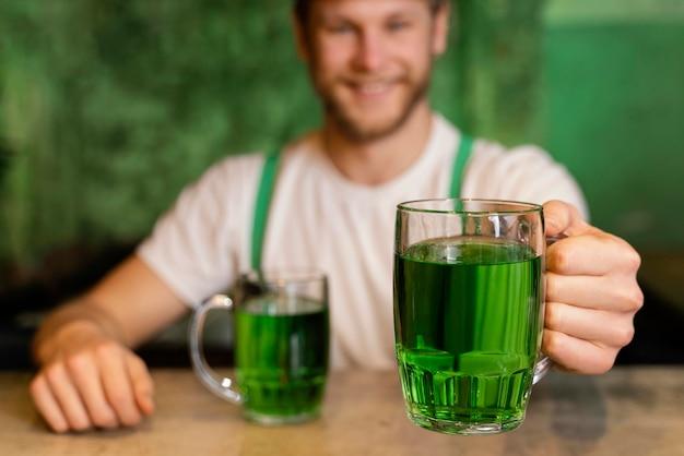 세인트를 축 하하는 잘 생긴 웃는 남자. 음료와 함께하는 패트릭의 날 무료 사진