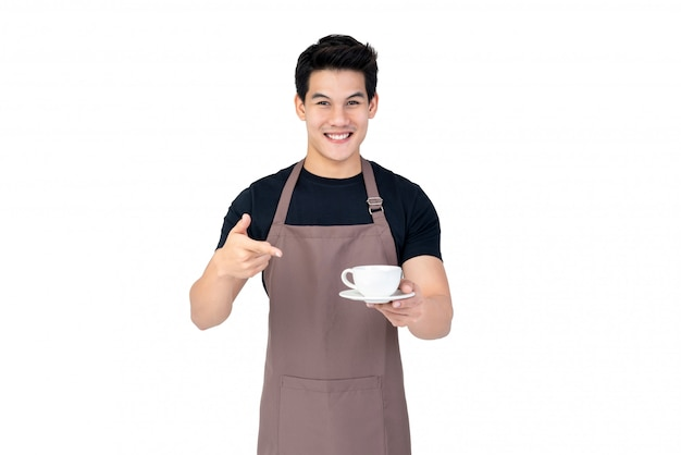 Handsome smiling asian barista serving coffee studio shot isolated on white background Premium Photo