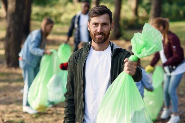 Красивый улыбающийся бородатый мужчина держит мешок для мусора на фоне своих друзей-активистов, собирающих мусор в парке Premium Фотографии