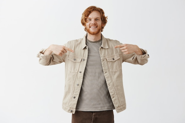 Handsome smiling bearded redhead guy posing against the white wall Free Photo