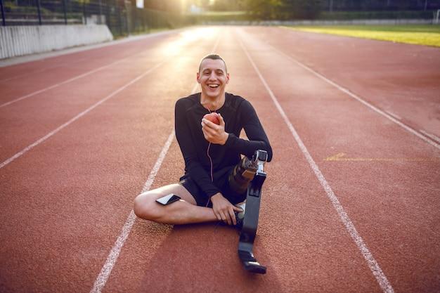 잘 생긴 웃는 백인 스포티 한 장애인 된 젊은 남자 운동복 및 경마장에 앉아 인공 다리, 음악 듣기 및 사과 먹는. 프리미엄 사진