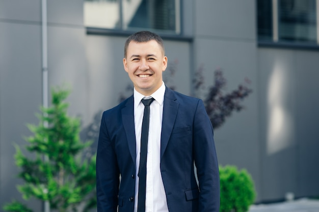 Handsome smiling confident businessman portrait. modern businessman. confident young man in suit looking away while standing outdoors with cityscape in the background. Premium Photo