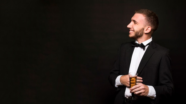Handsome smiling guy in dinner jacket with glass of drink Free Photo