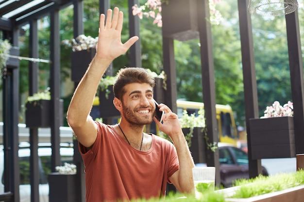 Bel ragazzo sorridente parlando al telefono e salutando la cameriera al caffè all'aperto, chiedendo il conto Foto Gratuite