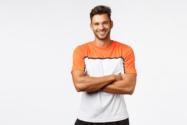 ハンサムな笑みを浮かべて男ボディービルダー、胸の上の腕を組んで、スポーツtシャツを着用します。 Premium写真