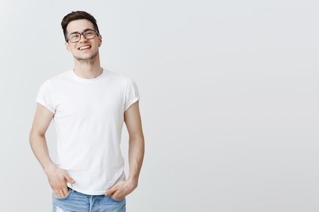 Bell'uomo sorridente in bicchieri in piedi Foto Gratuite