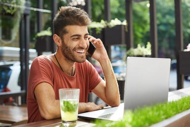 Красивый улыбающийся мужчина разговаривает по мобильному телефону, звонит продавцу, которого он нашел в интернете, используя ноутбук, делая покупки, ища квартиру в интернете Бесплатные Фотографии