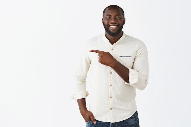 Bel ragazzo giovane sorridente in posa contro il muro bianco Foto Gratuite