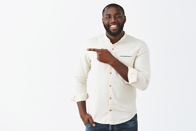 Handsome smiling young guy posing against the white wall Free Photo