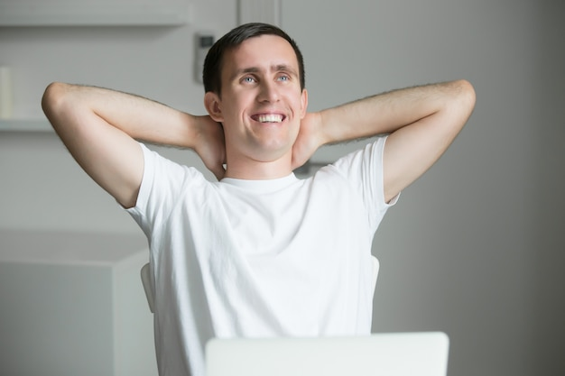 Handsome smiling young man outstretching at desk with laptop Free Photo