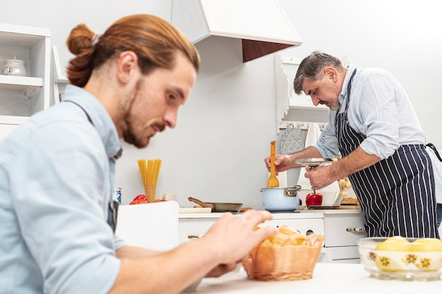 Handsome son and father cooking Free Photo