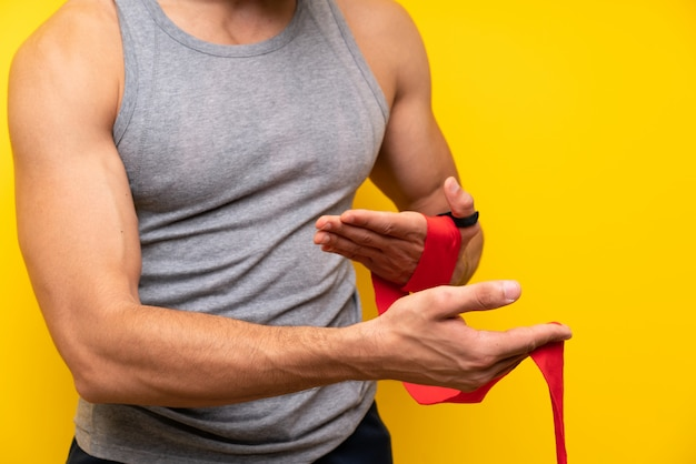 Handsome sport man over isolated wall in boxing bandages Premium Photo