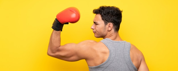 Handsome sport man over isolated wall with boxing gloves Premium Photo