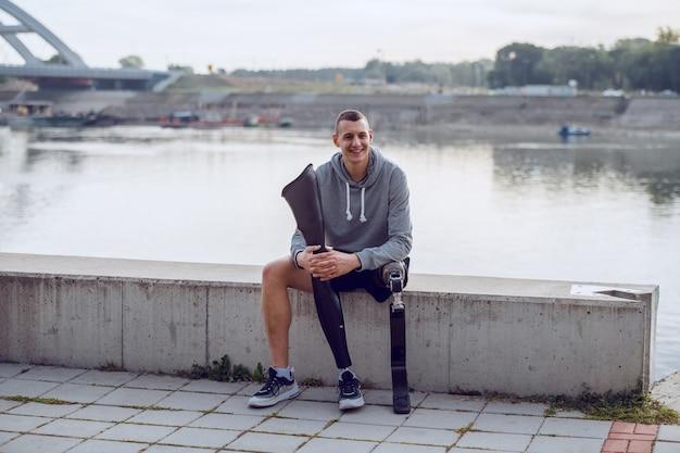スポーツウェアで、岸壁に座って別の義足を保持している義足のハンサムなスポーティな白人の障害を持つ男。 Premium写真