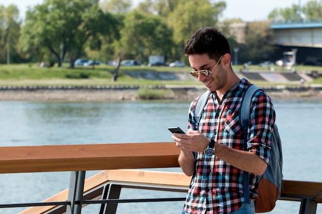 Handsome student uses a mobile phone beside the river. Premium Photo