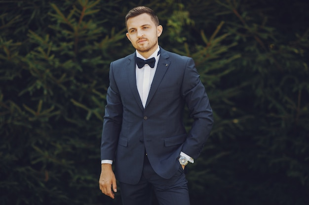 A handsome and stylish bride in a blue suit stands in a summer park near the bushes Free Photo