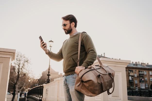 Uomo bello alla moda hipster che cammina in una strada cittadina con borsa in pelle utilizzando il telefono, viaggio indossando felpa e occhiali da sole, tendenza di stile urbano, giornata di sole Foto Gratuite