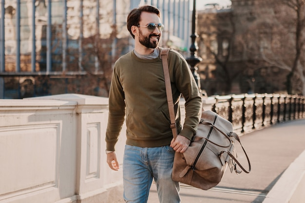 Handsome stylish hipster man walking in city street with leather bag wearing sweatshot and sunglasses, urban style trend, sunny day, smiling happy traveler Free Photo