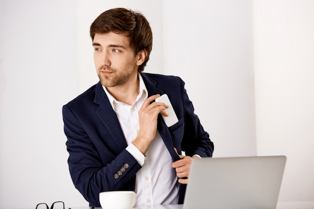 Handsome successful businessman sit office desk, drink coffee and check mail in laptop, put mobile phone in jacket pocket Free Photo