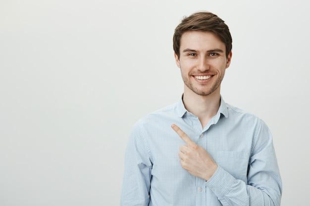 Красивый успешный мужчина-предприниматель, указывая пальцем в верхнем левом углу, улыбаясь Бесплатные Фотографии