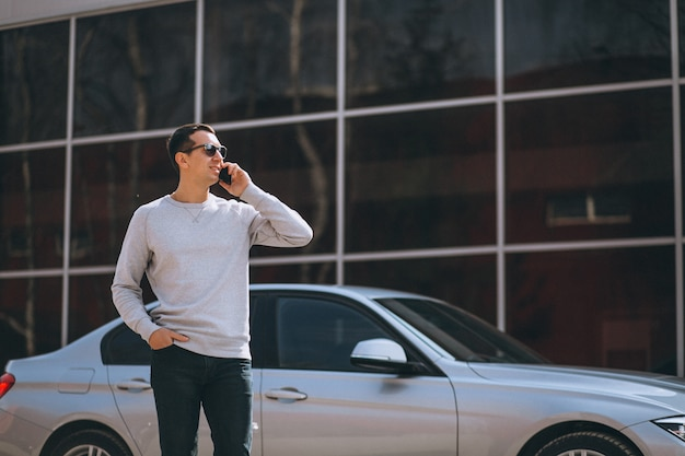 Handsome successful man by the car with cellphone Free Photo