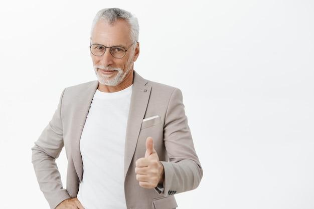 承認で親指を立てて示すハンサムな成功したシニアビジネスマン 無料写真
