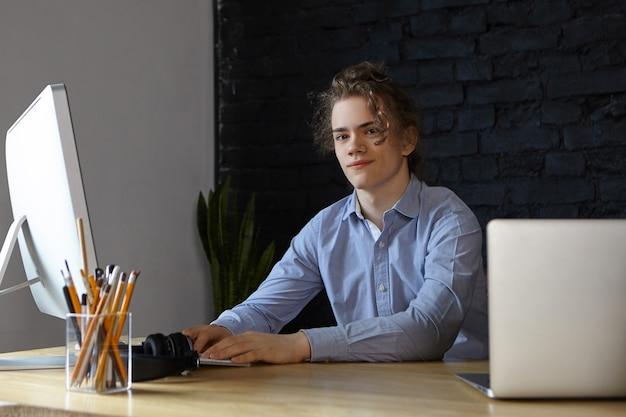 青いシャツの笑顔に身を包んだハンサムな成功した若い男性起業家、彼の職場で新しいスタートアップビジネスプロジェクトを開発し、素晴らしいアイデアと計画を持ち、最新の電子機器を使用 無料写真