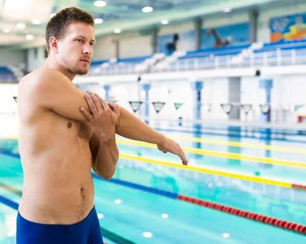 Handsome swimmer stretching medium shot Free Photo
