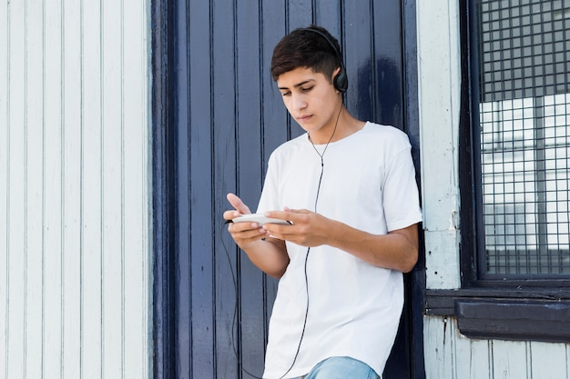 Handsome teenage boy leaning on metal wall using smartphone and listening music Free Photo