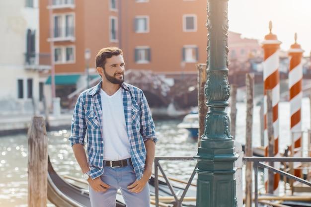 보트와 베네치아 Chanal에 아름다운 전망에 대해 부두에 서있는 잘 생긴 관광 남자 프리미엄 사진
