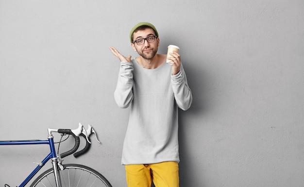 見知らぬ場所で自転車に乗った後、紙コップからコーヒーを飲み、不安を感じて肩を上げ、次の目的地を知らずにしばらく休んでいるハンサムな観光客。人とライフスタイル 無料写真