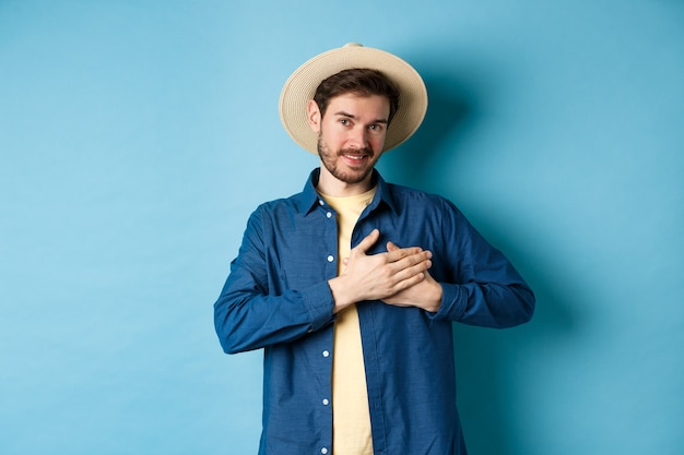 麦わら帽子をかぶったハンサムな旅行者、心に手をつないで笑顔、ありがとうのジェスチャーを示し、青い背景の上に立って、魂の中で休暇についての思い出を保ちます。 Premium写真