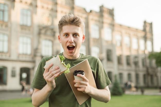 식욕을 돋우는 샌드위치를 먹는 잘 생긴 대학생 프리미엄 사진