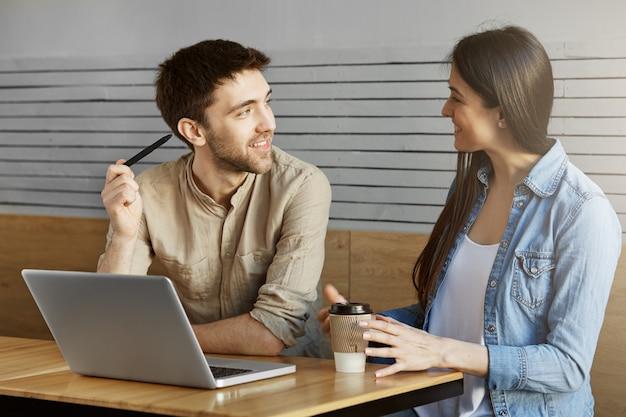 Красивый небритый мужской фрилансер сидя на встрече в кафе, показывая проект к клиенту и говоря о деталях работы. Бесплатные Фотографии