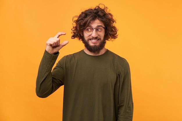 Bel maschio con la barba lunga con capelli ricci scuri e setole spesse, mostra qualcosa di minuscolo con le mani Foto Gratuite