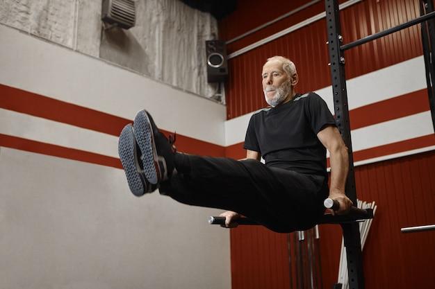 Красивый пенсионер usnhaven в стильной спортивной одежде занимается кроссфитом в тренажерном зале, поднимает ноги во время тренировки на перекладине, укрепляет брюшной пресс. концепция фитнеса, спорта и выхода на пенсию Бесплатные Фотографии