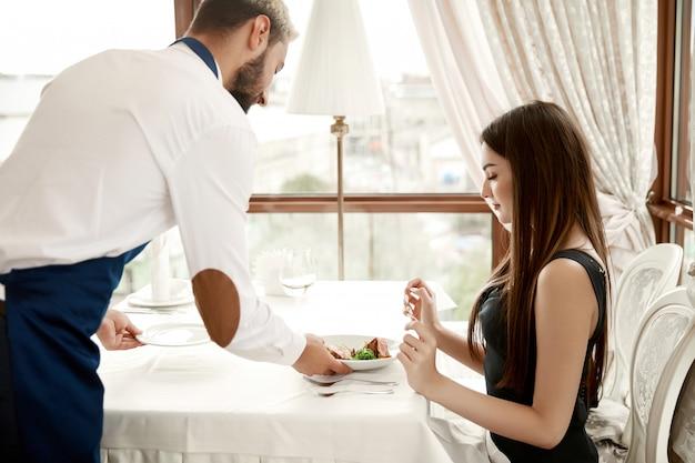 Красивый официант в ресторане подает молодой леди еду Бесплатные Фотографии