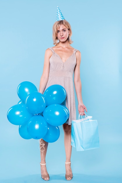 Handsome woman holding balloons and paper bags Free Photo
