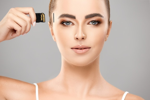 Handsome woman with light make-up and perfect skin holding memory card near temple on head, new technology world connected with human Premium Photo