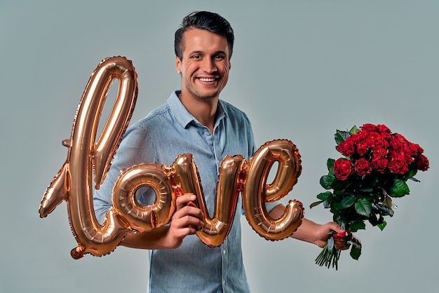 Handsome yound man in blue shirt is standing with red roses and air balloon labeled love in hand on grey. Premium Photo