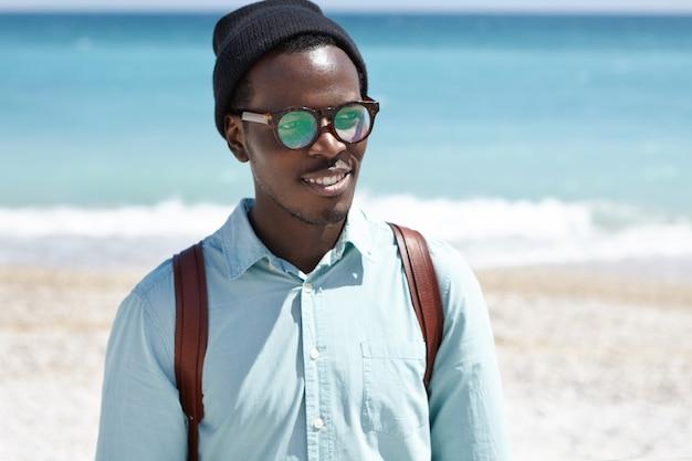海岸沿いを歩くハンサムな若いアフリカ系アメリカ人のヒップスター、広大な紺碧の海に背を向けて立っている天気の良い日と海の景色を眺める 無料写真