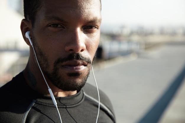 ハンサムな若いアフリカ系アメリカ人のランナーまたは朝の戸外で運動スポーツウェアを着てジョガー。彼のイヤホンを使用してトレーニングのためのやる気を起こさせる音楽を聴く魅力的な黒人男性 無料写真