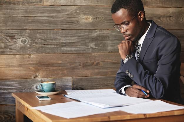 Красивый молодой африканский предприниматель читает контракт перед его подписанием Бесплатные Фотографии
