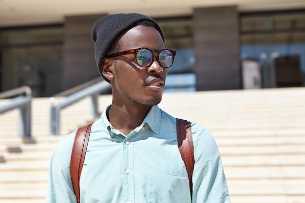 Bel giovane turista maschio africano che trasportano zaino esplorando le strade di sconosciuta città straniera durante le vacanze all'estero, edificio moderno e scale di cemento Foto Gratuite