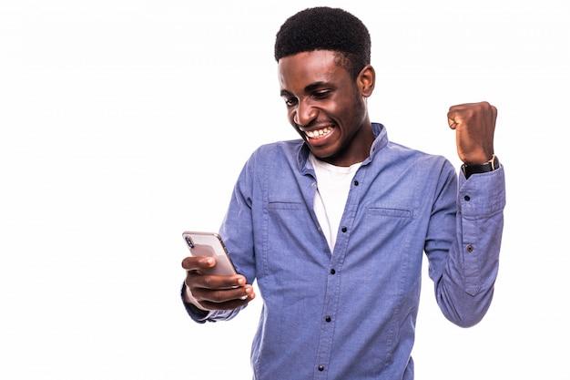 携帯電話を押しながら灰色の壁に立っている間身振りで示すハンサムな若いアフリカ人 無料写真