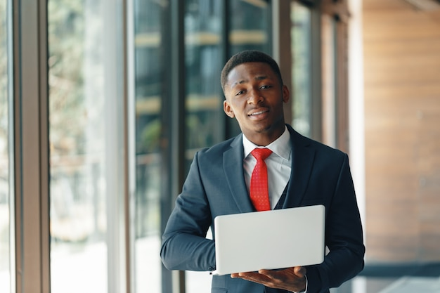 Handsome young afro american businessman in classic suit holding a laptop and smiling Premium Photo