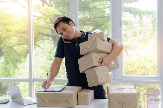 Handsome young asian delivery man happy after new order from customer Premium Photo