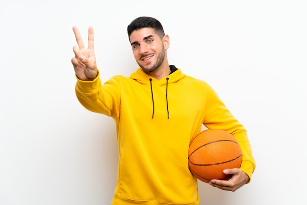 Handsome young basketball player man over isolated white wall smiling and showing victory sign Premium Photo