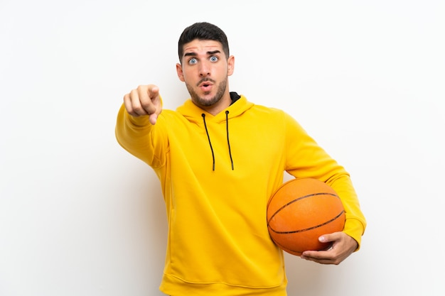 Handsome young basketball player man  on white wall surprised and pointing front Premium Photo