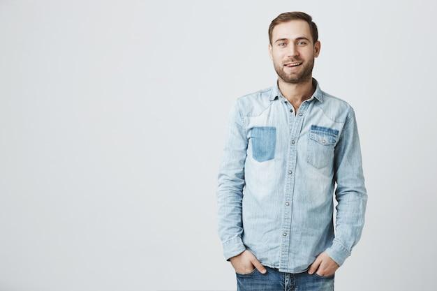デニムシャツでハンサムな若いひげを生やした男はポケットに手をつなぐ 無料写真